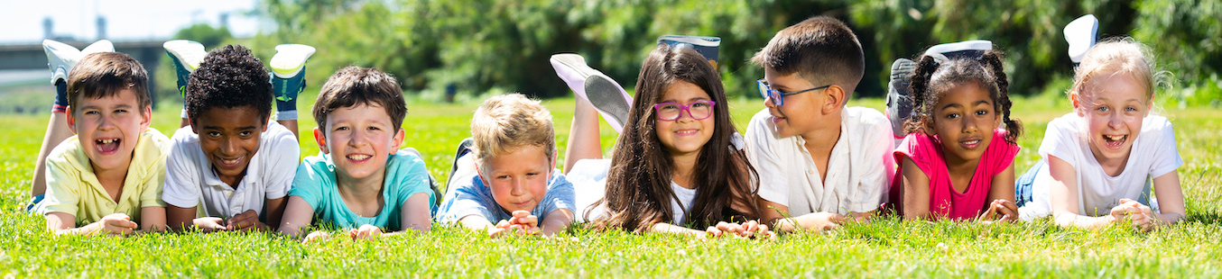 Happy team of friends children resting on grass together in park